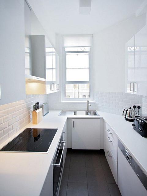 Nhà bếp không gian hẹp được thiết kế theo kiểu dáng chữ U tận dụng tối đa không gian. Thay vì làm nguyên hệ thống tủ bếp như thông thường thì chủ nhà đã bỏ đi tủ bếp trên để giúp không gian thêm phần thông thoáng